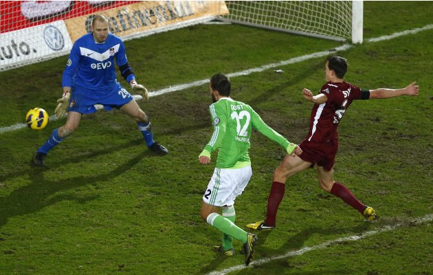 Bas Dost of Germany's first division Bundesliga club VfL Wolfsburg scores his team's first goal against goalkeeper Robert Wulnikowski of third division club Kickers Offenbach during their German socce