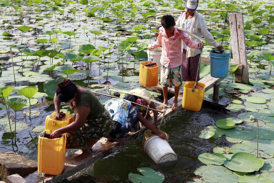 In this photo taken on April 21, 2012, local residents use plastic containers to fetch drinking water from a lake in Yangon, Myanmar. Earth Day is marked on Sunday, April 22, 2012. (AP Photo/Khin Maung Win)
