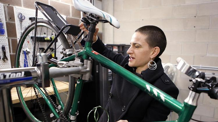 "In this photo taken Friday, Jan 11, 2013, Rose Barcklow works on her bike in the velo room at her apartment complex in downtown Denver. ""I decided to live without a car, to take the leap,"" said 31-year-old Rose Barcklow, who lives in a Denver apartment complex in a part of the city that gives her easy access to bike lanes she takes on her 7-mile bike commute to work. The complex, called Solera, is ueber-bike-friendly. She doesn't have to lug her two bikes up to her apartment because of its secure storage area for two-wheelers, and she makes use of the ""velo room,"" a tool-equipped workshop where she can pump up her tires, clean her chain, and fix a flat. (AP Photo/Ed Andrieski)"