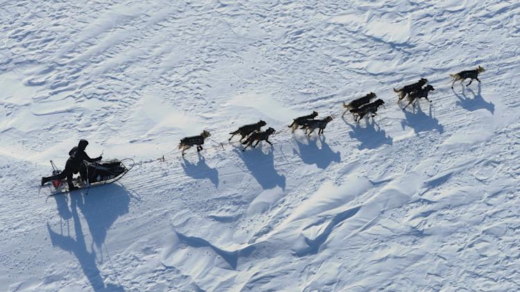 Dallas Seavey poles and kicks on the trail before reaching Elim, Alaska, during the Iditarod Trail Sled Dog Race on Monday, March 12, 2012. (AP Photo/Anchorage Daily News, Marc Lester)