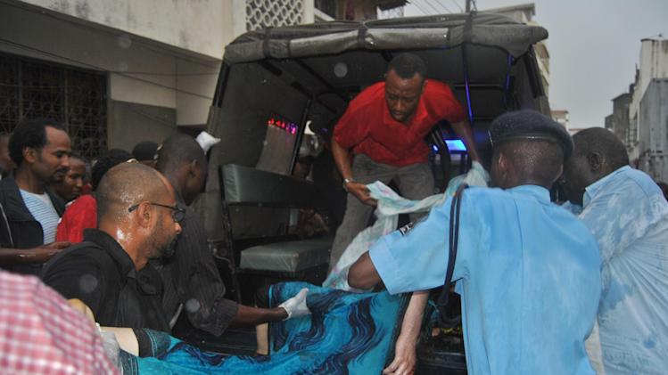 Kenyan police officers load the body of a female tourist into a police vehicle in Mombasa, Kenya, Thursday, July 24, 2014. A Kenya police official says a female tourist has been shot dead in the coastal town of Mombasa, the second foreigner shot in same area this month. (AP Photo)