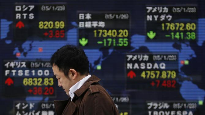 A man holding his mobile phone walks past an electronic board showing the stock market indices of various countries outside a brokerage in Tokyo