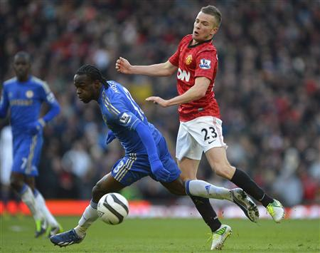 Manchester United's Cleverley challenges Chelsea's Moses during their English FA Cup quarter-final soccer match at Old Trafford in Manchester