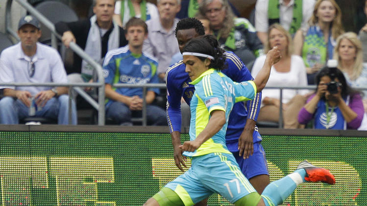 Seattle Sounders' Fredy Montero, shoots for a goal against the defense of Chelsea's John Mikel Obi in the first half of an exhibition soccer match, Wednesday, July 18, 2012, in Seattle. (AP Photo/Ted S. Warren)