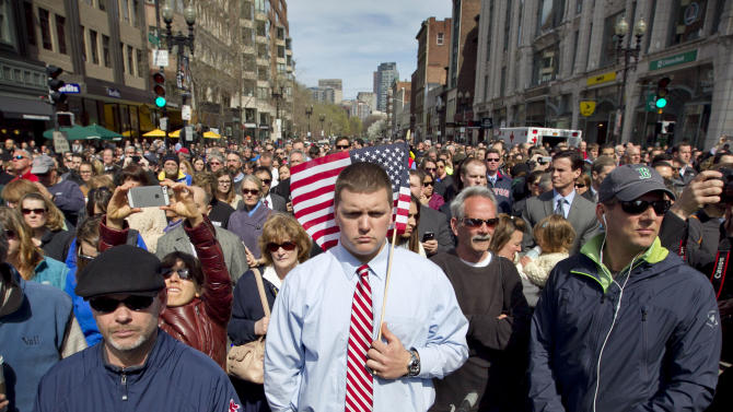 FILE - People observe a moment of silence in honor of the victims of the Boston Marathon bombing on Boylston Street near the race finish line, exactly one week after the bombings in Boston, Mass. on Monday, April 22, 2013. In just a four-month span, New England has been the backdrop for two incidents of mass carnage - the Dec. 14, 2012 shootings in Newtown, Conn., that killed 20 children and six staff members at Sandy Hook Elementary School and the Boston Marathon bombings on April 15, 2013 that killed three people and injured more than 260. (AP Photo/Robert F. Bukaty, File)