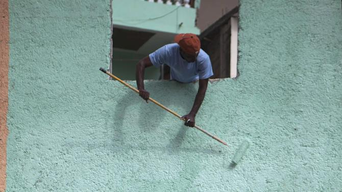 """In this March 21, 2013 photo, a worker paints blue the exterior wall of a home in Jalousie, a cinder block shantytown in Petionville, Haiti. The government's goal is to paint 1,000 homes and buildings as part of a $1.4 million effort titled """"Beauty versus Poverty: Jalousie in Colors,"""" a government project to relocate people from the displacement camps that sprouted up after Haiti's 2010 earthquake. (AP Photo/Dieu Nalio Chery)"""