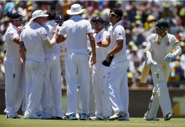 Australia's Clarke reacts as he walks past the England team celebrating his dismissal during the first day of the third Ashes cricket test in Perth