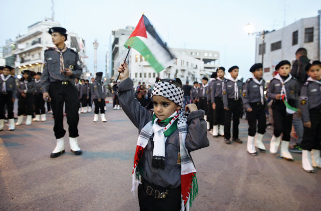 A Palestinian girl waves a flag during a rally supporting the Palestinian U.N. bid for observer state status, in the West bank city of Ramallah, Thursday, Nov. 29, 2012. The Palestinians are certain to win U.N. recognition as a state on Thursday but success could exact a high price: delaying an independent state of Palestine because of Israel's vehement opposition. (AP Photo/Majdi Mohammed)