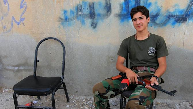 A Syrian rebel sits with his weapon on his knee in the rebel-held town of Tel Abyad, Syria , Friday, Oct. 5, 2012 which lies close to the Turkish Syrian border.  Turkey's state-run news agency says Turkish troops have returned fire after a mortar shell from Syria again landed on its territory. Turkish artillery has fired at Syrian targets for two straight days after shelling from Syria killed five civilians in Turkey. Turkey's parliament on Thursday also voted to allow cross border military operations in Syria. (AP Photo)