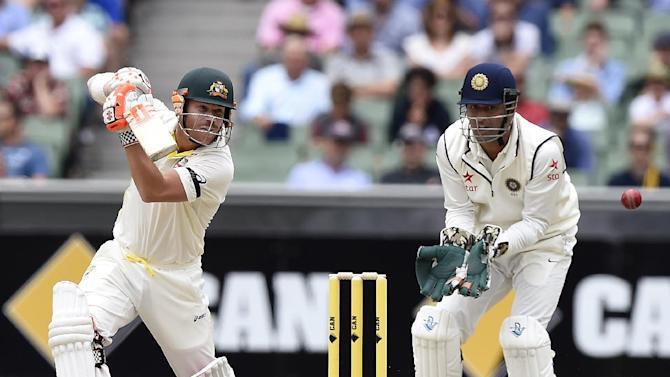 Australia's David Warner, left, cuts the ball in front of India's wicketkeeper MS Dhoni, right, on the fourth day of their cricket test match in Melbourne, Australia, Monday, Dec. 29, 2014. India are all out for 465 in reply to Australia's first innings of 530. (AP Photo/Andy Brownbill)