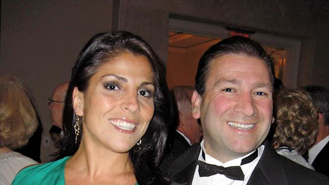 """In this May 16, 2011 photo Dr. Scott Kelley, right, and his wife Jill Kelley pose for a photo in Tampa, Fla. Jill Kelley's attempt to climb the Tampa social ladder _ the rungs of which included some high-ranking military officials _ has come to an ignominious halt. Accounts of lavish parties at her bayfront mansion have been replaced by reports of her family's financial woes and other dirty laundry, and claims that she traded on her acquaintance with David Petraeus to try to further lucrative business dealings. Now, even her """"Friends of MacDill"""" Air Force base access pass has been unceremoniously revoked. (AP Photo/Tampa Bay Magazine) MANDATORY CREDIT"""