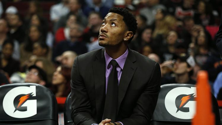 Chicago Bulls Derrick Rose watches the game from the bench against the San Antonio Spurs during the first half of an NBA basketball game on Tuesday, March 11, 2014, in Chicago. The San Antonio Spurs defeated The Chicago Bulls 104-96. (AP Photo/Andrew A. Nelles)