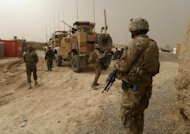US soldiers stand guard outside a military base near Alkozai village following the shooting of Afghan civilians allegedly by a US soldier in Panjwayi district, Kandahar province on March 11, 2012. The soldier allegedly left the base at night to commit the killings, which included nine children. He allegedly set several of their bodies on fire