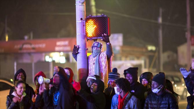 Protesters confront police officers during a second night of rioting in Ferguson, Missouri