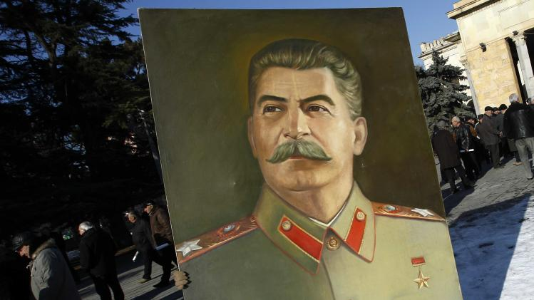 A man carries a portrait of Soviet dictator Josef Stalin as people attend a gathering marking the 130th anniversary of his birthday in Stalin's hometown town of Gori