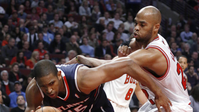 Atlanta Hawks center Al Horford (15) is pressured by Chicago Bulls forward Taj Gibson during the first half of an NBA basketball game Monday, Jan. 14, 2013, in Chicago. (AP Photo/Charles Rex Arbogast)