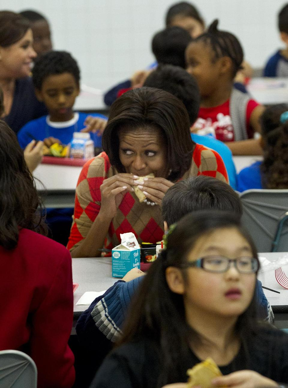 First lady Michelle Obama takes a bit of her turkey taco as she has lunch with school children at Parklawn Elementary School in Alexandria, Va. (AP Photo/Pablo Martinez Monsivais)