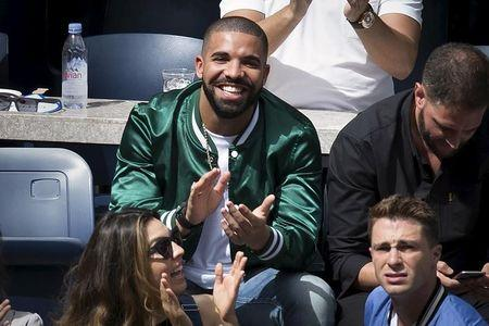 Musician Drake applauds as his image is displayed on the TV monitors during the Serena Williams, Roberta Vinci match at the U.S. Open Championships tennis tournament in New York