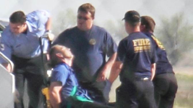 """Emergency workers tend to a JetBlue captain that had a """"medical situation"""" during a Las Vegas-bound flight from JFK International airport, Tuesday, March 27, 2012, in Amarillo, Texas. Passengers said the pilot screamed that Iraq or Afghanistan had planted a bomb on the flight, was locked out of the cockpit, and then tackled and restrained by passengers. The pilot who subsequently took command of the aircraft elected to land in Amarillo at about 10 a.m., JetBlue Airways said in a statement. (AP Photo/Steve Douglas)"""