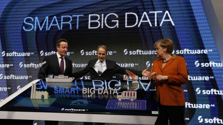 Streibich, CEO of Software AG welcomes British PM Cameron and German Chancellor Merkel during a tour at the CeBIT technology fair in Hanover