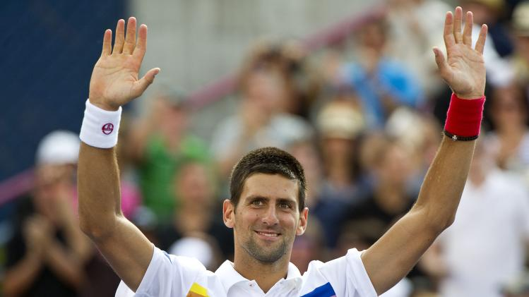 Novak Djokovic from Serbia waves following his 7-5, 6-2 victory over Marin Cilic from Croatia, at the Rogers Cup men's tennis tournament Thursday, Aug. 11, 2011 in Montreal. (AP Photo/The Canadian Press, Paul Chiasson)