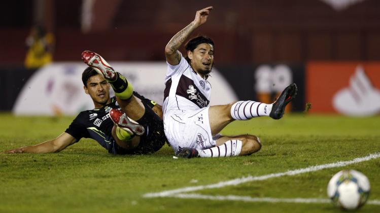 Blanco of Argentina's Lanus and Alanis of Mexico's Santos Laguna fight for the ball during their Copa Libertadores soccer match in Buenos Aires
