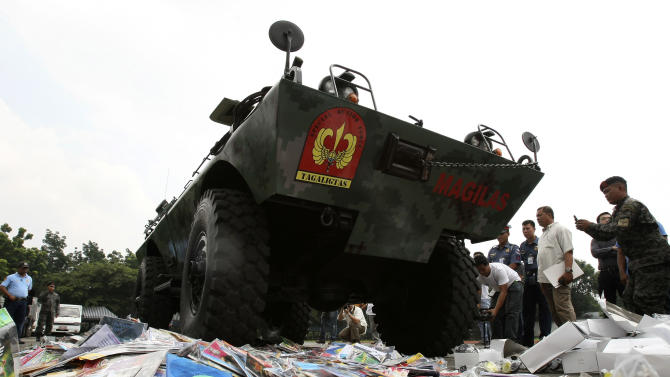 An Armored Personnel Carrier of the Philippine National Police runs over piles of pirated DVDs and counterfeit sunglasses during ceremonial destruction of counterfeit goods seized in raids recently at parade grounds of the police headquarters at suburban Quezon city, northeast of Manila, Thursday June 30, 2011. The ceremonial destruction of pirated DVDs and other counterfeit goods was done to coincide with the global celebration and awareness campaign known as World Anti-Counterfeiting Day. (AP Photo/Bullit Marquez)