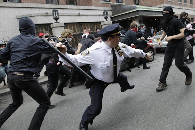 A police lieutenant swings his baton at an Occupy Wall Street activists on Tuesday, May 1, 2012 in New York.  Hundreds of activists with a variety of causes spread out over New York City Tuesday on In