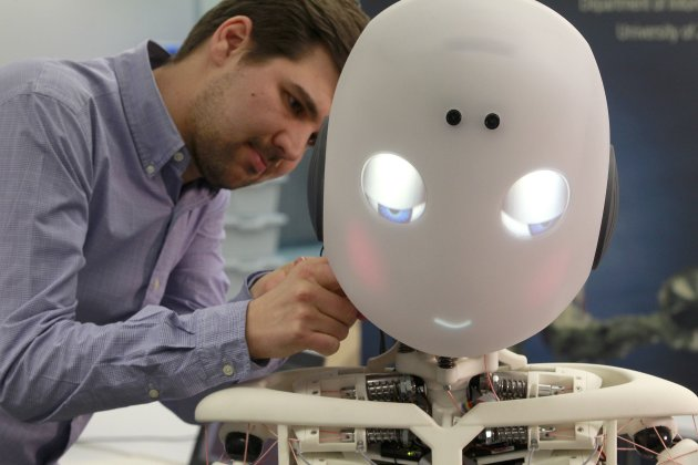 Dominik Brumm of the Artificial Lab of the University of Zuerich checks humanoid robot ROBOY during a media presentation in Zurich