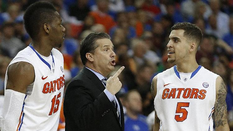 Kentucky head coach John Calipari speaks as Florida forward Will Yeguete (15) and Scottie Wilbekin (5) walk on the court during the second half of an NCAA college basketball game in the Championship round of the Southeastern Conference men's tournament, Sunday, March 16, 2014, in Atlanta