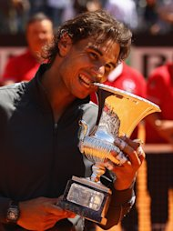 ROME, ITALY - MAY 21:  Rafael Nadal of Spain bites the trophy after defeating Novak Djokovic of Serbia in their final match during day ten of the Internazionali BNL d'Italia 2012 at the Foro Italico Tennis Centre on May 21, 2012 in Rome, Italy.  (Photo by Clive Brunskill/Getty Images)