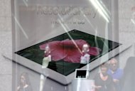 <p>Pedestrians walk past an Apple store advertising the iPad. The US technology giant has paid $60 million to a Chinese firm to settle a long-running dispute over the iPad trademark in China, a court said Monday.</p>
