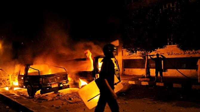 A riot policeman passes a burning vehicle during clashes outside the U.S. embassy in Cairo, Egypt, early Thursday, Sept. 13, 2012, as part of widespread anger across the Muslim world about a film ridiculing Islam's Prophet Muhammad. (AP Photo/Hussein Talal)