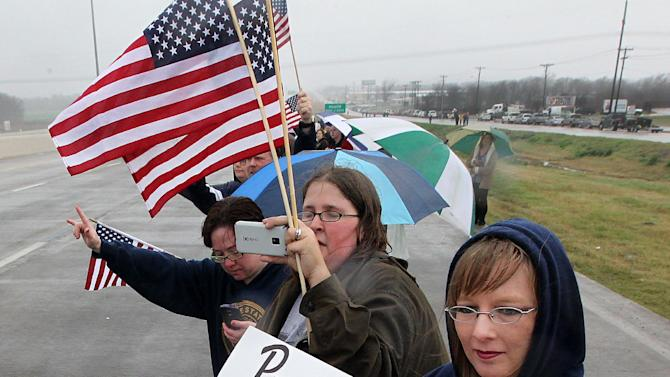 Christine Warren holds a sign in memory of former Navy seal Chris Kyle as hundreds turn out in the rain along Interstate 35 to pay their respects as the funeral procession passed through Waco, Texas,  Tuesday, Feb. 12, 2013, for his final journey to Austin, where he will be buried at the Texas State Cemetery. Kyle and his friend Chad Littlefield were shot and killed Feb 2. at a North Texas gun range. (AP Photo/Waco Tribune Herald, Jerry Larson)