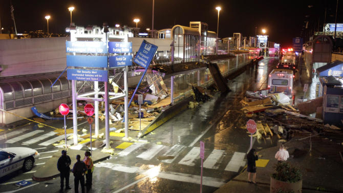 Storm damage is seen next to a parking garage outside terminal one at St. Louis International Airport Friday, April 22, 2011, in St. Louis. Several people at Lambert Airport in St. Louis were injured Friday after an apparent tornado touched down, spewing debris over the airfield, bursting glass in the concourse and damaging cars atop a parking garage. (AP Photo/Jeff Roberson)