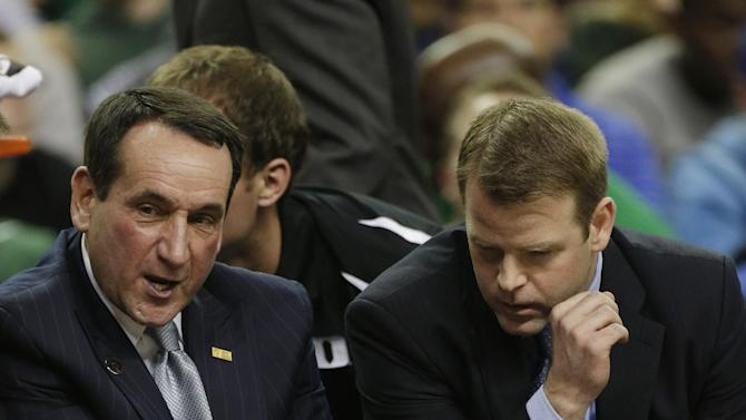 Duke coach Mike Krzyzewski holds his knee after falling out of his chair during a time out during the second half of an NCAA college basketball game against Kentucky at the Georgia Dome in Atlanta Tuesday, Nov. 13, 2012. (AP Photo/Dave Martin)