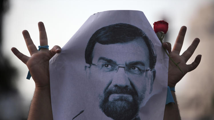 A supporter of the Iranian presidential candidate Mohsen Rezaei, a former Revolutionary Guard commander, holds up his poster with a rose, in a street campaign, in Tehran, Iran, Sunday, June 9, 2013. The presidential election will be held on June 14. (AP Photo/Vahid Salemi)