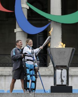 Claire Lomas lights the Paralympic flame cauldron in Trafalgar Square in London, Friday, Aug. 24, 2012. Claire had a horse riding accident in 2007 leaving her paralysed from the chest down. The London Paralympics begin on Wednesday Aug. 29. (AP Photo/Kirsty Wigglesworth)
