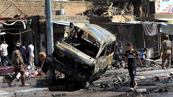 People and security forces inspect the site of a car bomb explosion in Basra, 340 miles (550 kilometers) southeast of Baghdad, Iraq, Monday, July 29, 2013. A wave of over a dozen car bombings hit central and southern Iraq during morning rush hour on Monday, killing scores in the latest coordinated attack by insurgents determined to undermine the government. (AP Photo/ Nabil al-Jurani)