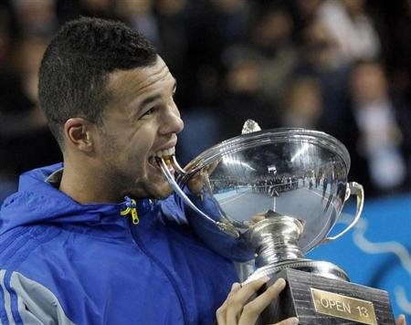 France's Tsonga bites his trophy after winning his match against Berdych of Czech Republic in the final of the Open 13 tennis tournament in Marseille