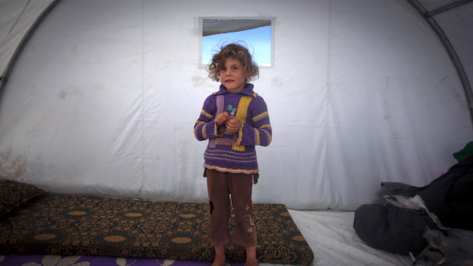 In this Wednesday, Nov. 7, 2012 photo, Shaymaa Al-Sadi, 6, who fled with her family from the violence in their village, poses for a photograph inside a tent at a displaced camp, in the Syrian village of Atmeh, near the Turkish border with Syria. Most of the displaced people in the tent camp rising near this village on the Syrian-Turkish border are children. All have fled the violence of Syria's civil war further south. Many have seen violence themselves, some have lost relatives, and most have trouble sleeping and panic when they hear loud noises or airplanes, their parents say. The Atmeh camp was born of necessity about three months ago, say the local rebels who run the place, distributing tents and food aid provided by a smattering of aid organizations.(AP Photo/ Khalil Hamra)