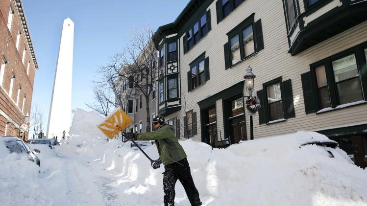 Jared Joiner shovels out his car in the shadow of the Bunker Hill monument in the Charlestown neighborhood of Boston Sunday, Feb.10, 2013. (AP Photo/Winslow Townson)