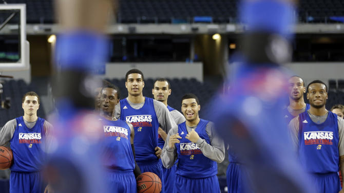 Kansas players react as Jamari Traylor dunks during practice for a regional semifinal game in the NCAA college basketball tournament, Thursday, March 28, 2013, in Arlington, Texas. Kansas faces Michigan on Friday. (AP Photo/David J. Phillip)