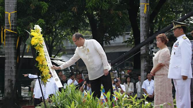 Philippine President Benigno Aquino III, left, arranges a wreath during ceremonies marking the 115th Philippine Independence Day at Liwasang Bonifacio, a square named after Filipino revolutionary leader Andres Bonifacio a in Manila, Philippines on Wednesday June 12, 2013. Aquino vowed Wednesday his country will not back down from any challenge to its sovereignty and territory amid a sea dispute with China. (AP Photo/Aaron Favila)