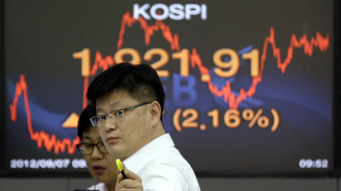 Currency traders talk to each other near a screen showing the Korea Composite Stock Price Index (KOSPI) at the foreign exchange dealing room of the Korea Exchange Bank headquarters in Seoul, South Korea, Friday, Sept. 7, 2012. Asian stock markets rallied Friday, boosted by strong advances on Wall Street and a highly anticipated plan to assist debt-riddled countries in the eurozone. (AP Photo/Lee Jin-man)