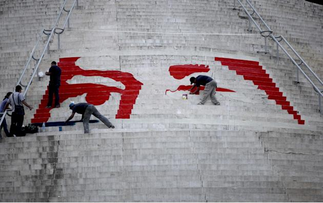 Workers paint a mural that is symbolic of the eyes of Venezuela's late President Hugo Chavez on the stairs at the El Calvario monument in Caracas, Venezuela, Thursday, March 7, 2013.  Chavez died on M