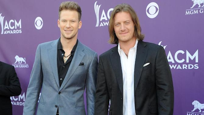 "FILE - This April 7, 2013 file photo shows Brian Kelley, left, and Tyler Hubbard, of the musical group Florida Georgia Line at the 48th Annual Academy of Country Music Awards at the MGM Grand Garden Arena in Las Vegas. Florida Georgia Line thought they were riding the whirlwind when their first single improbably made it to the top of the country charts late last year. Now that rapper Nelly has entered the picture and ""Cruise"" is rocketing up the pop charts, Tyler Hubbard and Brian Kelley have discovered _ like Taylor Swift, Lady Antebellum and a few other country acts over the years _ there's nothing like the ride of a crossover hit. (Photo by Al Powers/Invision/AP, file)"