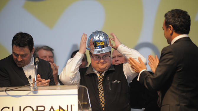 IMAGE DISTRIBUTED FOR CHOBANI - Marc Abjean, senior vice president, global engineering and project management for Chobani, reacts as he receives a silver hard hat from Hamdi Ulukaya, founder and chief executive officer of Chobani, Monday, Dec. 17, 2012, in Twin Falls, Idaho. The hat was given as a token of appreciation for his efforts in building the world's largest yogurt manufacturing plant in just 326 days.  (Photo by Jack Dempsey/Invision for Chobani/AP Images)