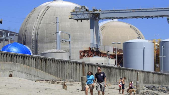 FILE - This file photo taken June 30, 2011, shows beach-goers walking on the sand near the San Onofre nuclear power plant in San Clemente , Calif. A leak of non-radioactive ammonia at the plant Tuesday afternoon prompted  a precautionary evacuation of workers. (AP Photo, Lenny Ignelzi, File)