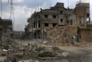 Rubble litters a street in the battered city of Qusayr, southwest of Homs, in western Syria on June 20. A Syrian pilot was granted political asylum after landing his MiG fighter jet in neighbouring Jordan, in the first such defection of a revolt a watchdog says has killed more than 15,000 people